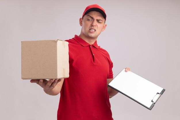 Insatisfait jeune livreur en uniforme avec capuchon tenant le presse-papiers en regardant la boîte dans sa main isolé sur un mur blanc
