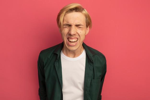 Insatisfait jeune mec blond vêtu d'un t-shirt vert tenant les mains sur la taille