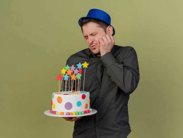 Insatisfait avec les yeux fermés jeune homme de fête portant une chemise noire et un chapeau bleu tenant un gâteau mettant la main sur la joue isolé sur vert olive