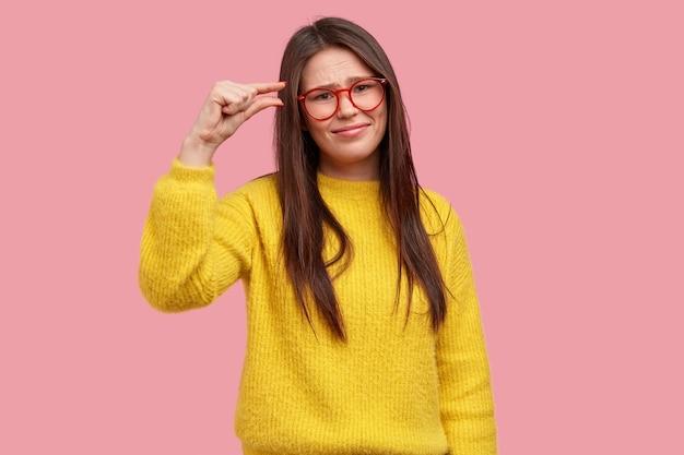 Insatisfaite jeune femme a les cheveux longs, décrit la taille avec les doigts, montre quelque chose de peu, porte des lunettes optiques, un pull jaune chaud