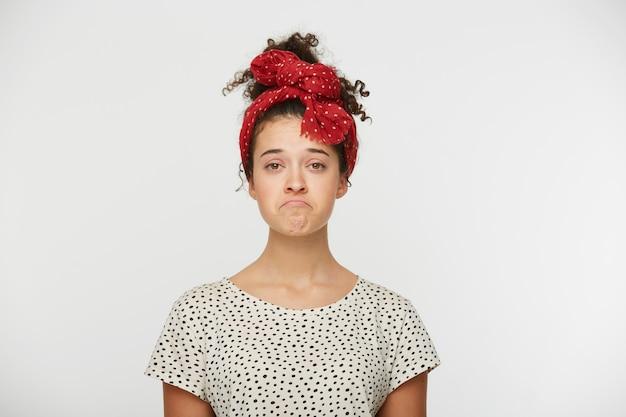 Insatisfaite jeune femme pincée la lèvre inférieure, maltraitée par quelque chose de désagréable