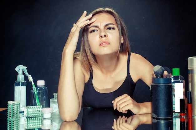 Insatisfaite malheureuse jeune femme se regardant dans un miroir sur fond noir. concept de peau et d'acné roblem