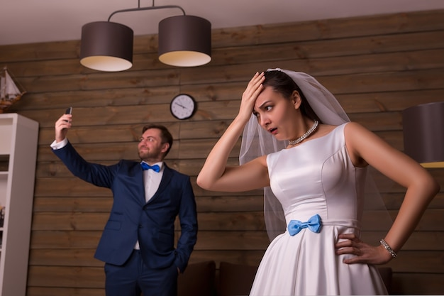 Insatisfaits mariés faisant selfie sur chambre en bois