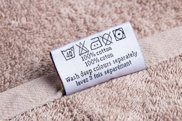 L'inscription 100% des chats sur une serviette éponge allongée sur un fond rose