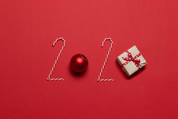 Inscription 2020 de divers objets décorés boule de boules de verre rouge classique, canne en bonbon sur un fond rouge