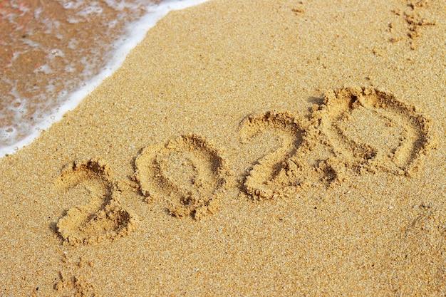Inscription 2020 sur le sable doré en gros plan, vue de dessus