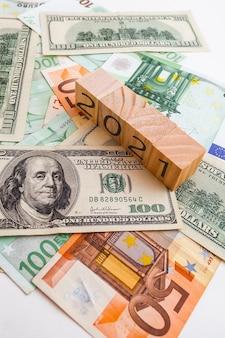 Inscription 2021 sur des cubes en bois sur la texture des dollars américains et des billets en euros