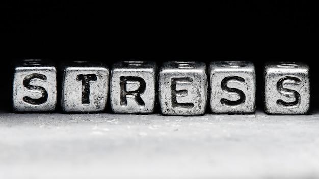 Inscription 3d stress sur cubes métalliques sur un fond gris noir strict, concept de résistance au stress