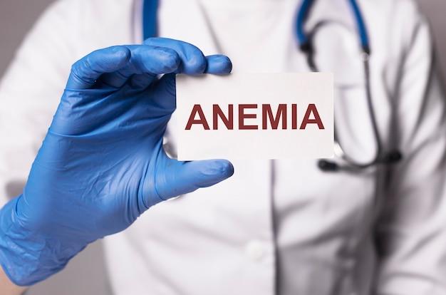 Inscription d'anémie sur papier dans la main du médecin en gros plan de gants bleus