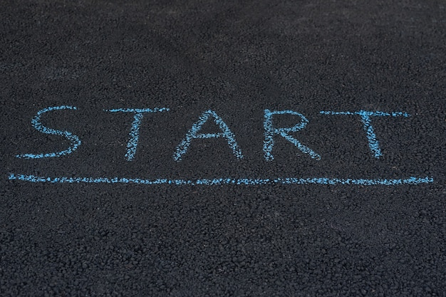 Inscription sur l'asphalte start. avis sur la chaussée. baissez la tête et lisez le message important.