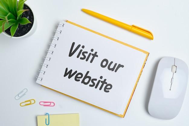L'inscription sur l'autocollant visitez notre site web comme un concept de publicité sur internet.