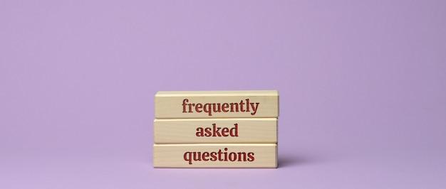 Inscription aux questions fréquemment posées sur des blocs de bois sur une surface violette