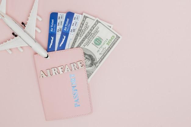 Inscription billet d'avion, avion, billet d'avion et argent sur fond rose. concept de voyage, espace copie
