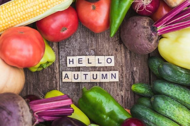 L'inscription bonjour l'automne sur le fond de l'humeur d'automne des légumes frais de la ferme et de la nourriture d'automne