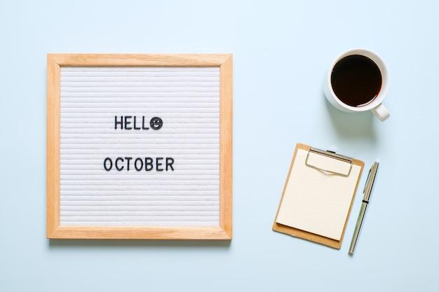 Inscription bonjour octobre sur tableau blanc, avec des feuilles sèches sur fond bleu clair. notion d'automne