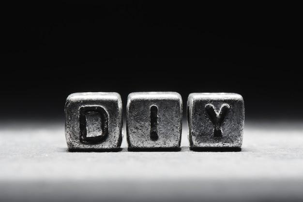 Inscription bricolage sur des cubes de métal dans le style grunge sur fond noir ñ'ðµð¼ð½ð¾ ñ ðµñ € ñ ‹ð¹ isolé