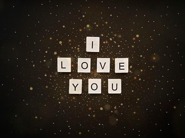 L'inscription des carrés en bois je t'aime sur un beau fond noir avec des paillettes d'or. notion romantique. style plat.