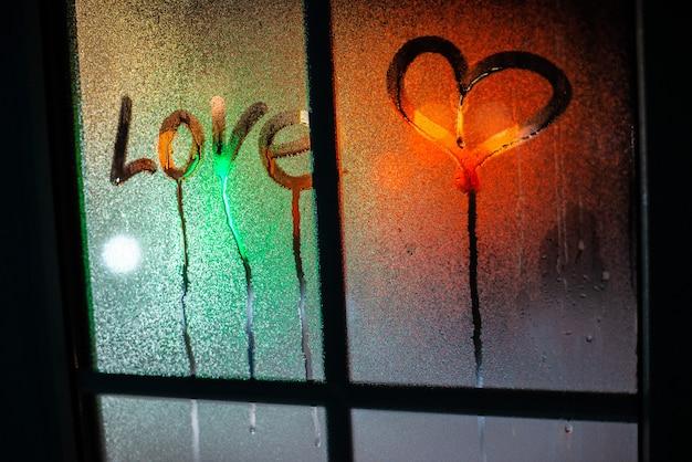 Inscription coeur et amour sur le verre embué contre
