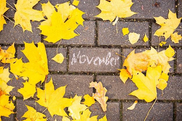 Inscription à la craie novembre sur la tuile d'asphalte parmi les feuilles d'automne vue de dessus