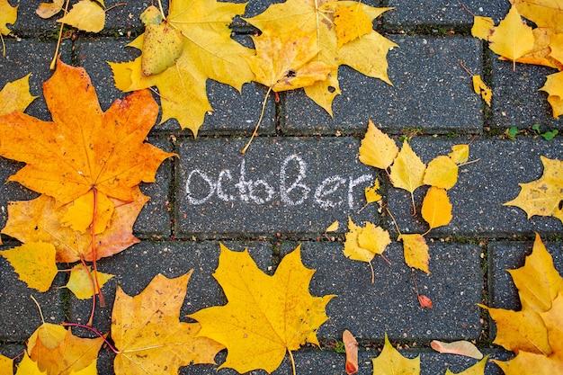 Inscription à la craie octobre sur la tuile d'asphalte parmi les feuilles d'automne. vue de dessus. concept automne tombant