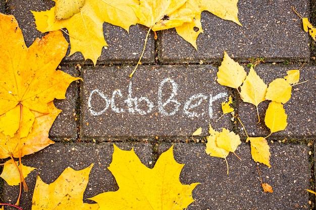 Inscription à la craie octobre sur la tuile d'asphalte parmi les feuilles d'automne vue de dessus