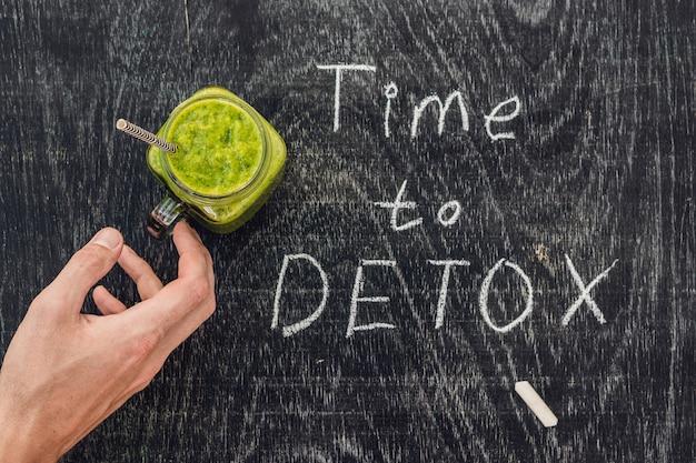 Inscription à la craie time to detox sur la table en bois et smoothies verts aux épinards. concept de saine alimentation et de sport.