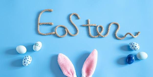 Inscription créative de pâques sur bleu avec des éléments de décor de pâques.