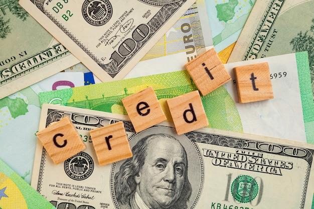 Inscription de crédit sur des cubes en bois sur la texture des dollars américains et des billets en euros