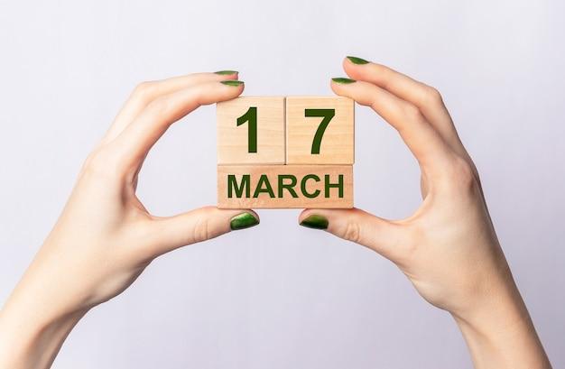 Inscription du 17 mars sur le calendrier en bois entre les mains des femmes.