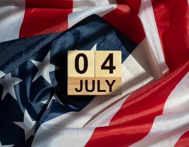 Inscription du 4 juillet sur le calendrier en bois sur le drapeau américain. jour de l'indépendance.