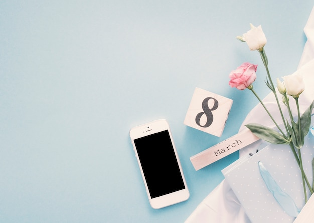 Inscription du 8 mars avec des fleurs et smartphone sur table