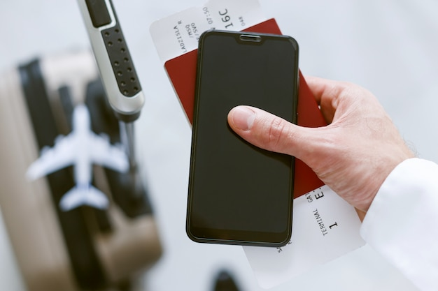 Inscription électronique via smartphone pour embarquer dans l'avion. homme avec une valise détient un billet de téléphone et un passeport.