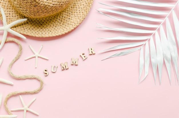Inscription d'été avec chapeau de paille et feuille de palmier
