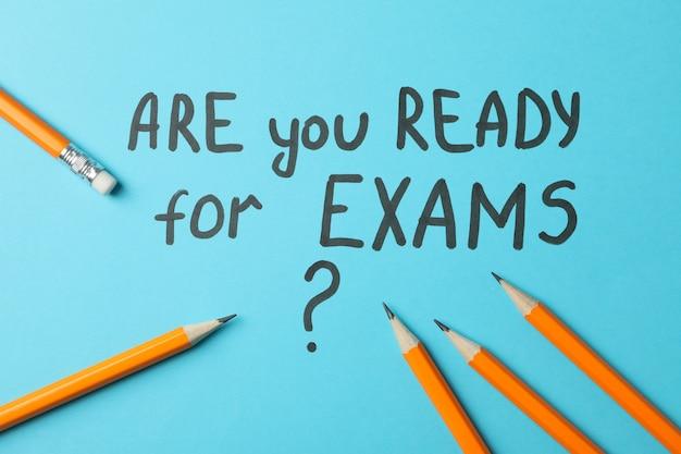 Inscription êtes-vous prêt pour les examens et les crayons sur la surface bleue, vue de dessus