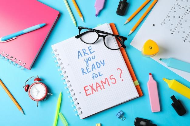 Inscription êtes-vous prêt pour les examens et stationnaire sur la surface bleue, vue de dessus