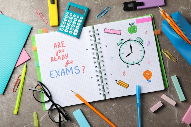 Inscription êtes-vous prêt pour les examens? et stationnaire sur une surface grise, vue de dessus