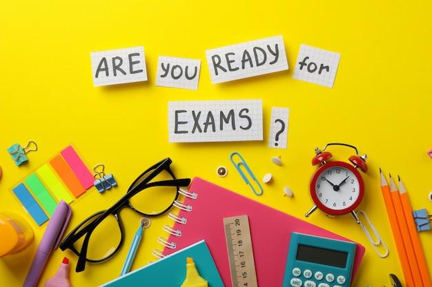 Inscription êtes-vous prêt pour les examens? et stationnaire sur une surface jaune, vue de dessus