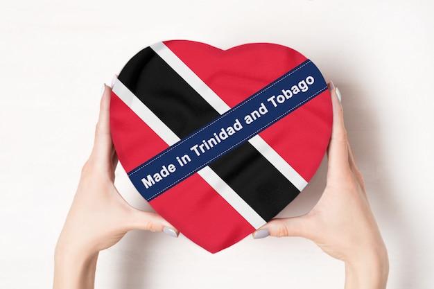 Inscription faite à trinité-et-tobago le drapeau de trinité-et-tobago. mains féminines tenant une boîte en forme de coeur. .