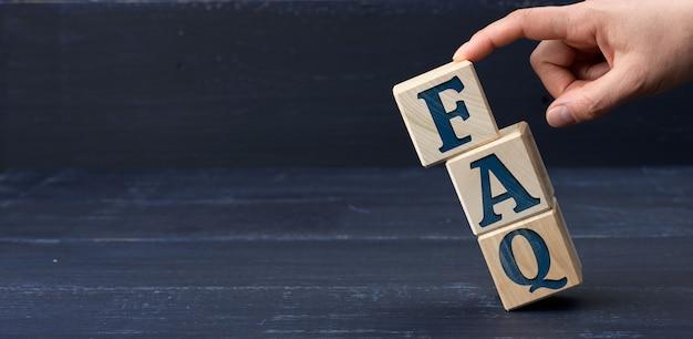 Inscription faq (questions fréquemment posées) sur des blocs de bois sur une surface bleue