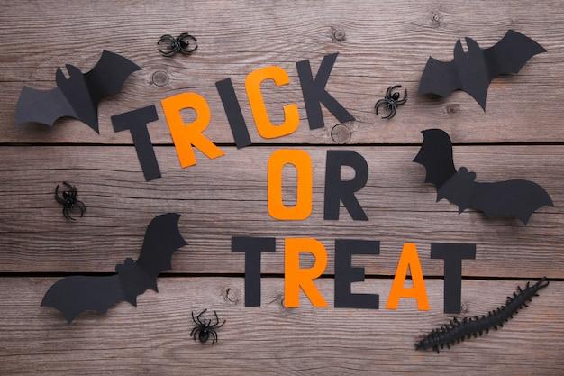 Inscription halloween avec des chauves-souris en papier avec des araignées sur un fond en bois gris. halloween