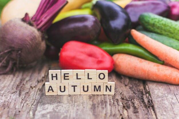 L'inscription hello autumn sur fond de légumes frais de la ferme. humeur d'automne et nourriture d'automne, légumes et végétarisme