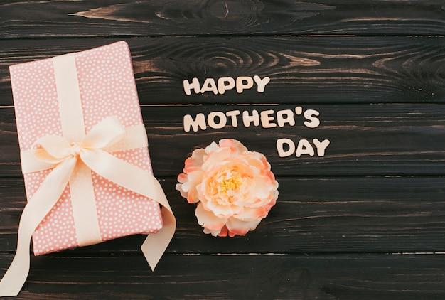 Inscription heureuse fête des mères avec boîte-cadeau et fleur