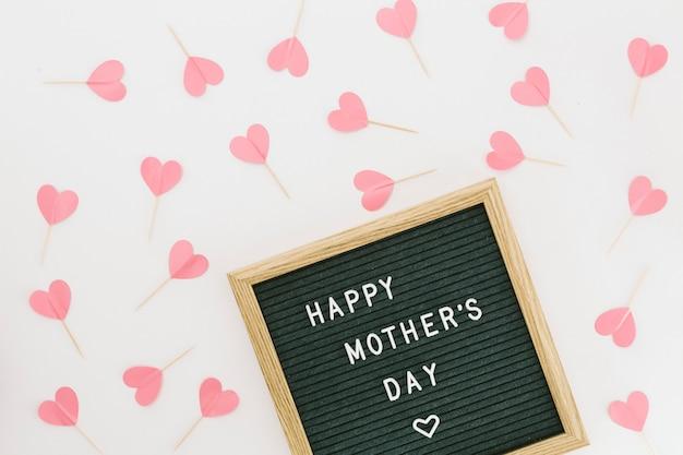 Inscription heureuse fête des mères à bord avec des coeurs de papier