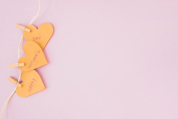 Inscription heureuse fête des mères sur les cœurs épinglés à la corde