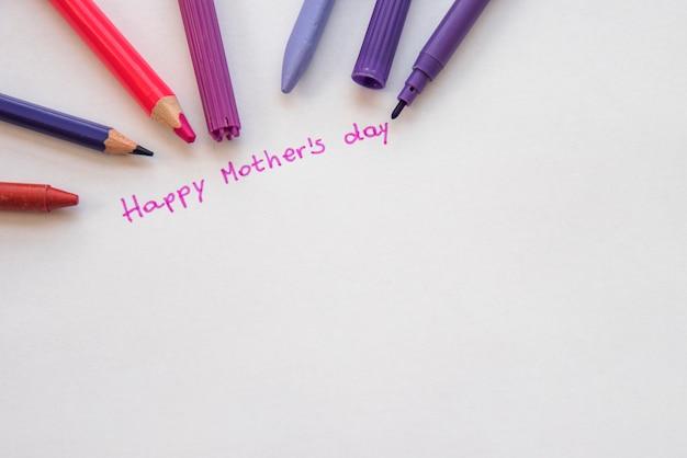 Inscription heureuse fête des mères avec des crayons sur papier