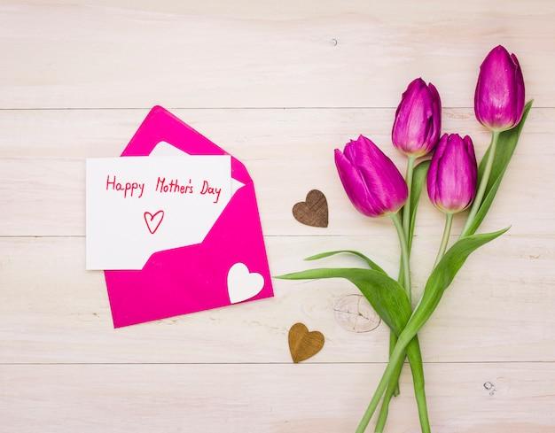 Inscription heureuse fête des mères dans l'enveloppe avec des tulipes