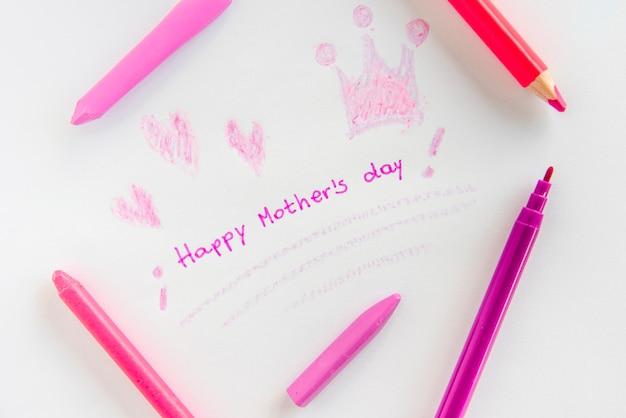 Inscription heureuse fête des mères avec des dessins et des crayons
