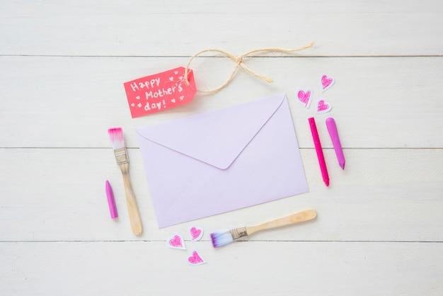 Inscription heureuse fête des mères avec enveloppe et pinceaux
