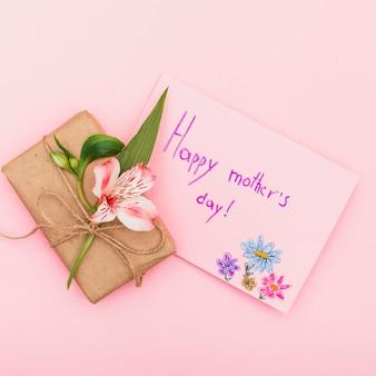 Inscription heureuse fête des mères avec fleur et cadeau