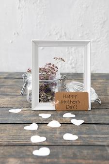 Inscription heureuse fête des mères avec des fleurs et un cadre